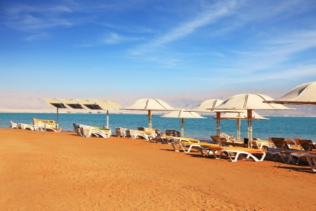 Beautiful sunny day at a beach resort. Dead Sea, the orange sand and beach chairs waiting for tourists photo