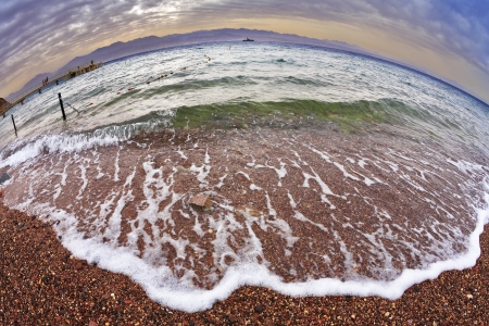 fenced in: Early spring on a beach of Red sea in Israel. The safe place for bathing is fenced. It is photographed by an objective the Fish eye