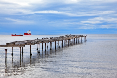 strait of magellan: Abandoned pier. Old dilapidated pier in the Strait of Magellan. In the distance the two cargo ships