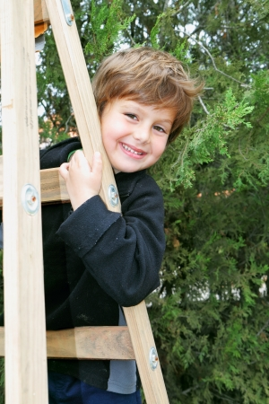 climbed: A charming four year old boy climbed a wooden extension ladders in the garden