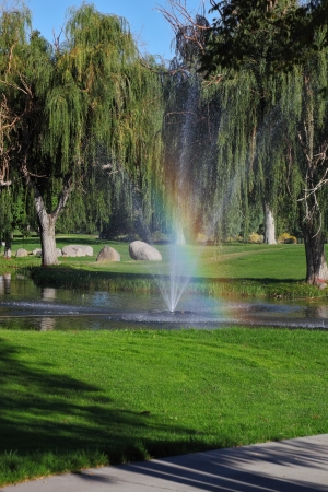 Decorative fountain and shining rainbow on the golf course photo