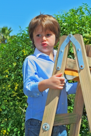 climbed: The beautiful green-eyed boy spoiled by attention climbed up a wooden sliding ladder