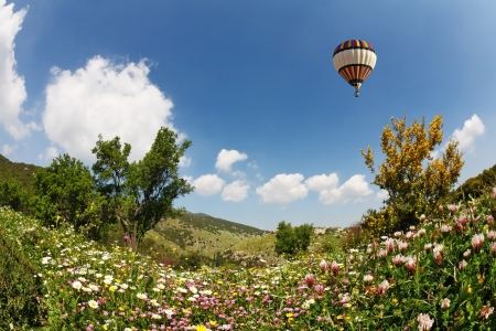 A huge bright balloon flying over scenic hills, blooming buttercups photo