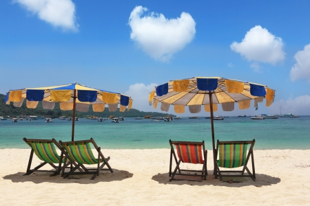 Beach paradise on island Phi-Phi, Thailand. Multi-colored beach umbrellas and convenient chaise lounges wait for tourists  photo