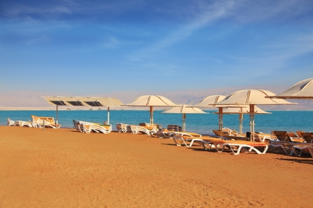 Magnificent beach with pure yellow sand on the bank of the Dead Sea  For visitors of hotel - beach umbrellas and beach plank beds photo