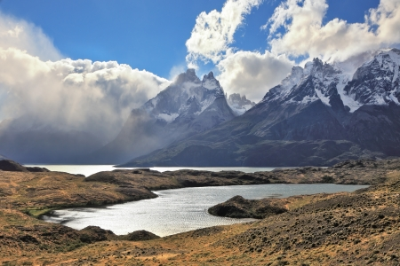 envelops: The majestic landscape of Patagonia  National Park Torres del Paine  Fog envelops the mountain range and is reflected in the cold water of the lake