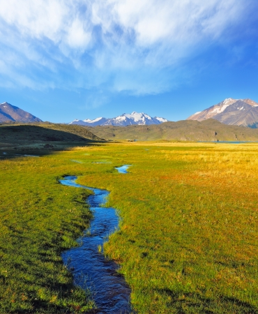 perito: A solitary Estancia in the national park Perito Moreno in Argentina. A huge valley surrounded by snow-capped mountains. Crosses the picturesque valley of the creek Stock Photo