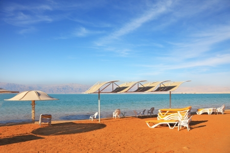 Beautiful sunny day at a beach resort  Dead Sea, the orange sand and beach chairs waiting for tourists photo