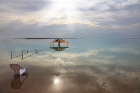 Medical beach on the Dead Sea, Israel  Round gazebo and a beach chair in the water  Cloudy sky reflected in water photo