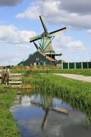 The village - an ethnographic museum in Holland. The picturesque windmill  is reflected in the channel photo