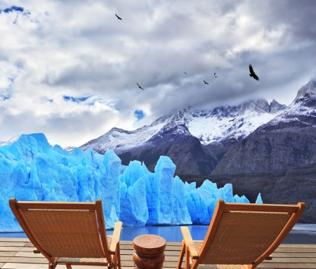 Two folding wooden chairs and a small bedside table on the boardwalk. A comfortable place to enjoy the beauty of the enormous Perito Moreno glacier in Argentina. photo