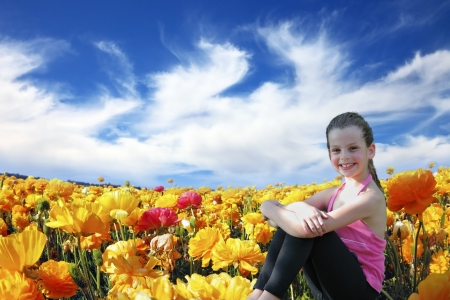 Charming beautiful six year old girl sitting and smiling in a field of blossoming yellow and red buttercups photo