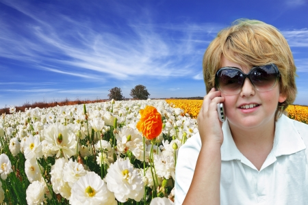 Beautiful blond boy with sunglasses talking on his mobile phone. Behind him, the field of buttercups blooming garden photo