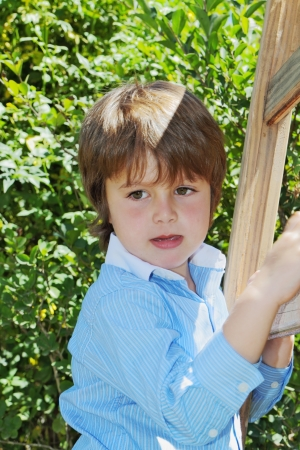 climbed: The spoiled beautiful green-eyed boy climbed up a wooden sliding ladder and doesnt want to go down
