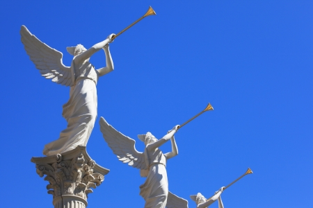 The statues of winged troubadours against the blue sky decorated capitals of the columns photo