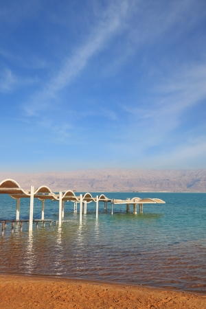 Descent in water is issued by a picturesque canopy and a handrail  Magnificent beach on the bank of the Dead Sea  photo
