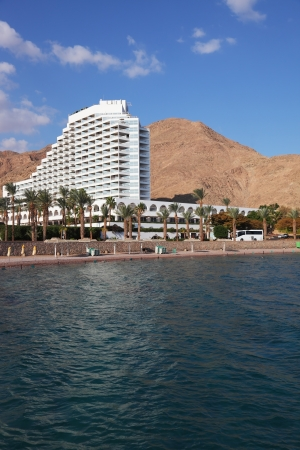Resort on coast of Red sea. Magnificent snow-white hotel, palm trees and mountains