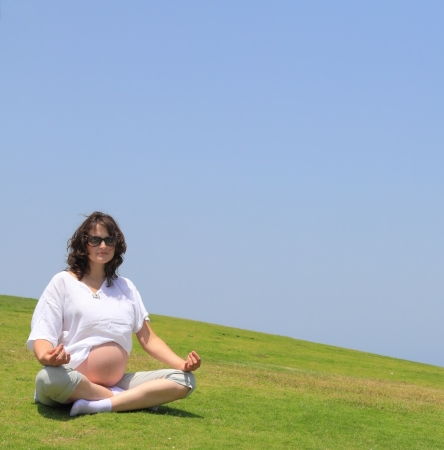 Happy young pregnant woman doing yoga on the lawn by the sea. photo