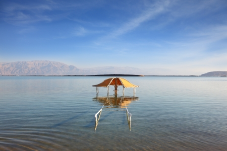 The magnificent beach on the Dead Sea  The picturesque gazebo for protection from the sun reflected in water photo