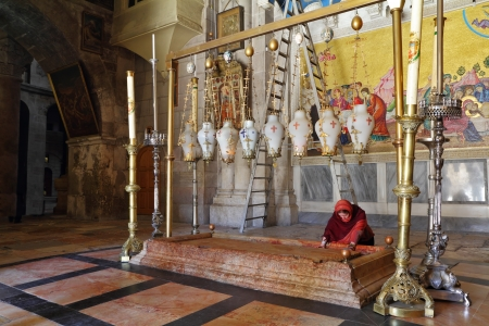 passionately: The pilgrim in red clothes passionately prays under icon lamps.  Temple of the Holy Sepulcher in Jerusalem. The oldest Christian sanctuary - Stone of Unction.  Editorial