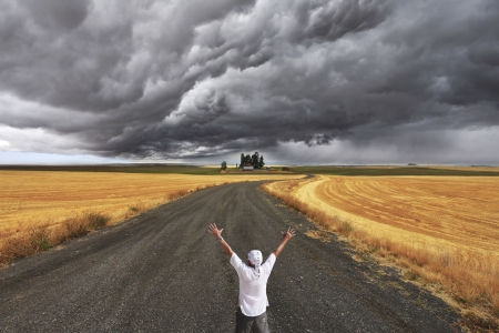 The enthusiastic tourist welcomes thunderstorm above Montana. Fields after a harvest and road photo