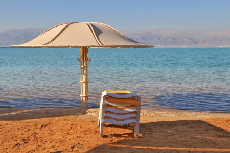 Sunny beach on the Dead Sea. A wonderful warm day in December. Beach umbrella and deck chair waiting for tourists photo