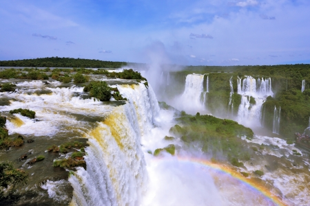 The roaring waterfalls in South America - Iguazu. Blanker jet fall between green jungle. Magnificent rainbow shines in the mist photo