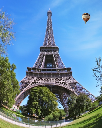 Hugel Eiffel Tower. At the foot of the tower is designed park with paths and pond. In the sky next to the tower floats giant balloon. The picture was taken Fisheye lens photo