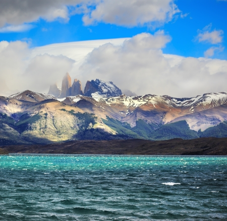 Fantastic beauty of the national park Torres del Paine in Chilean Patagonia  Strong wind drives wave in Laguna Azul emerald water  On the horizon are seen the famous cliffs of Torres