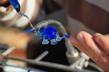 Delicate work of the glass blower  The Artist-glass blower produces a graceful tiny figure of an elephant from color glass Stock Photo