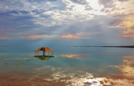 Efectos �pticos excelente y reflejos de las nubes y el sol en el invierno el agua en el mirador Muerto Mar Rojo en el agua cerca de la orilla Foto de archivo - 24087433