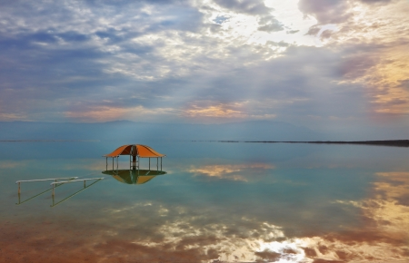 Efectos ópticos excelente y reflejos de las nubes y el sol en el invierno el agua en el mirador Muerto Mar Rojo en el agua cerca de la orilla Foto de archivo - 24087433