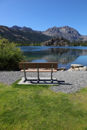 Cosy bench on the shore of Gull Lake. A bright sunny day, the mountain is reflected in the smooth water of the lake photo