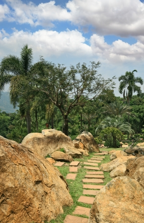 Masterpiece of landscape design - huge and fine park in Thailand  Palm trees, stone boulders and the path which has been laid out by tiles photo