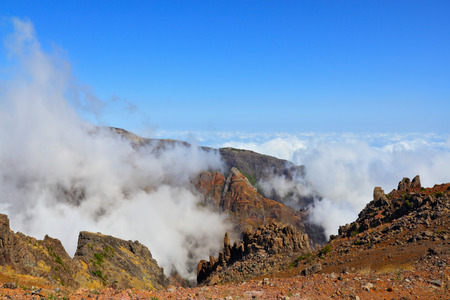 The highest peak of Madeira Island - Pico Ruyvu. A very strong wind at the top of the volcanic island of Madeira is driving the cloud Stock Photo - 26258036