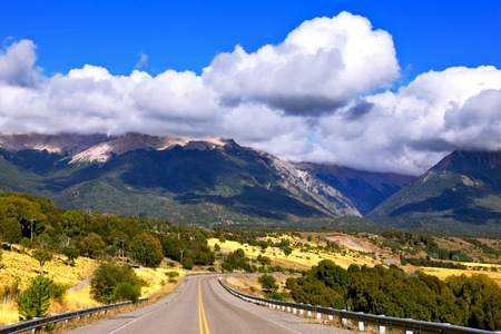 ruta: Patagonia. The longest road the Ruta 40 passes in Argentina among lakes and fields. Magnificent cumulus clouds decorate mountains of the Southern Andes