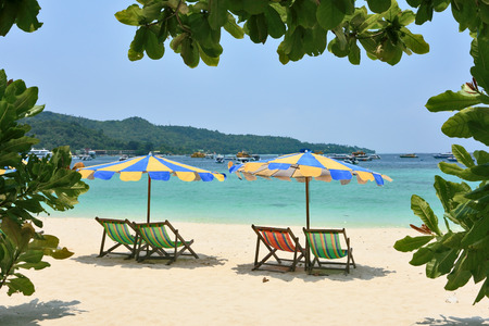 Tropical paradise on the bank of the azure sea. Multi-colored beach umbrellas and chaise lounges on white sand  photo
