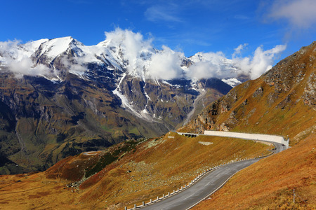 Famous picturesque views of the road in Austrian Alps - Grossglocknershtrasse. Ideal highway winds high in the mountains. The highest mountain peaks covered with fresh snow photo