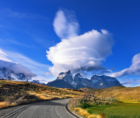 Amazing sunset in the Chilean Patagonia. Fabulous clouds over cliffs Los Kuernos in national park Torres del Paine. The dirt road leads to the mountain range photo