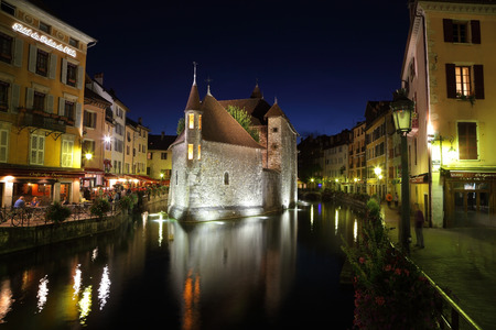 The capital of the Haute-Savoie - Annecy  The main attraction of the city - an ancient fortress-prison on an island in the middle of the river  Fortress beautifully lit and is reflected in the smooth water  photo
