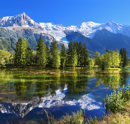 City park in the mountain resort of Chamonix in France. Snowy mountains and evergreen spruce reflected in the lake