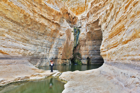 ein: Beautiful gorge in the Negev desert. Ein Avdat Canyon, a female photographer taking pictures scenic landscape