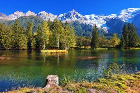 Lake with cold water surrounded by trees and snow-capped mountains. City park in the Alpine resort of Chamonix Reklamní fotografie