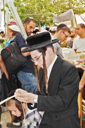 sukkot: GERUSALEMME, ISRAELE - 18 settembre 2013: la giovane Ebreo religioso con lunghi boccoli sceglie con cura pianta rituale - mirto per Sukkot.