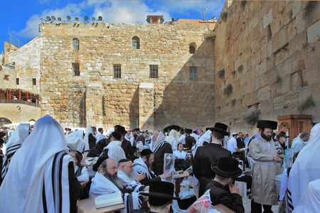 sukkoth festival: JERUSALEM, ISRAEL - SEPTEMBER 20, 2013: Morning Sukkot.  The Western Wall of the Temple in Jerusalem. Many religious Jews in traditional robes tallit gathered for prayer.