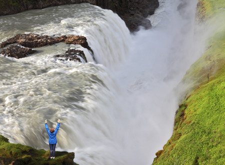 chasm: The delighted woman - tourist over  water chasm. Enormous falls Gyullfoss. Summer in Iceland Stock Photo