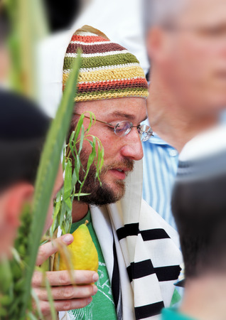 etrog: JERUSALEM, ISRAEL - SEPTEMBER 20, 2013:  Young religious Jew in a knitted skullcap and talite with citrus-etrog praying in the morning of Sukkot. The Western Wall of the Temple in Jerusalem
