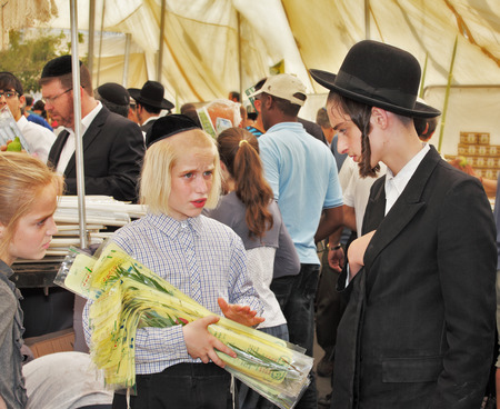 sukkoth festival: JERUSALEM, ISRAEL - SEPTEMBER 18, 2013: Big market on the eve of the Jewish holiday of Sukkot. The boy - teenager with long blond hair and a black velvet skullcap sells ritual plants Editorial
