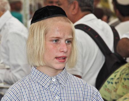 sukkot: GERUSALEMME, ISRAELE - 18 settembre 2013: Grande mercato alla vigilia della festa ebraica di Sukkot. Il ragazzo - adolescente con lunghi capelli biondi e un velluto papalina nera