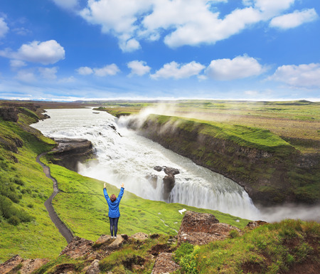 Delighted woman tourist on the shore of the waterfall. Gyullfoss, Iceland photo